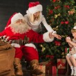 Photo of cute girl and her mother and Santa Claus at home   — Stock fotografie