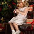 Happy little girl with Christmas gifts sitting near Christmas tree — ストック写真