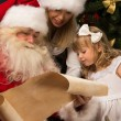 Santa Claus sitting at home with cute little girl and her mother — Stok fotoğraf