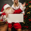Santa Claus holding white blank sign with his wife and helper — Stock Photo #36111723