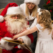 Stock Photo: Santa Claus sitting at home with family - little girl and her mother