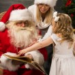 Santa Claus sitting at home with family - little girl and her mother — Stock Photo