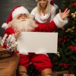 Santa Claus holding white blank sign with his wife and helper — Stock Photo