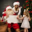 Santa Claus holding white blank sign with family   — Stock Photo