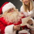 Portrait of happy Santa Claus sitting at home with his helper — Stock Photo