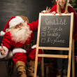 Santa Claus with his helper standing near chalkboard with wishlist — Zdjęcie stockowe