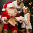 Santa Claus sitting at home with cute little girl and her mother — Stock Photo #36112211