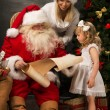 Santa Claus sitting at home with cute little girl and her mother — Stock Photo