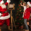 Santa Claus taking picture of cheerful woman with little girl — Stock Photo