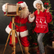 Santa Claus taking picture of cheerful woman with old wooden camera — Stock Photo
