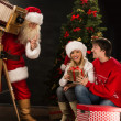 Santa Claus taking picture of couple with old wooden camera — Stock Photo #36112459