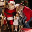 Santa Claus taking picture of couple with old wooden camera — Stockfoto