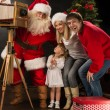Santa Claus taking picture of couple with old wooden camera — Foto de Stock