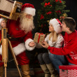 Santa Claus taking picture of couple with old wooden camera — Stock Photo #36112543