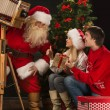 Santa Claus taking picture of couple with old wooden camera — Stock Photo