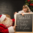 Santa Claus with child sitting near chalkboard with wish list — Stock Photo #36112709