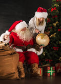 Santa Claus and his wife or helper holding globus and discussing — Stock Photo