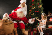 Photo of cute girl and her mother and Santa Claus at home — Stock Photo