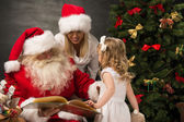Santa Claus sitting at home with family - — Foto Stock