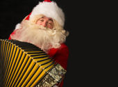 Santa Claus sitting in armchair at home and playing music on accordion — Stock Photo