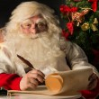 Santa Claus sitting at home and writing a letter — Stock Photo #36520091