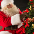 Santa Claus decorating Christmas tree in dark room  — Stock Photo