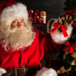 Santa Claus decorating Christmas tree in dark room — Stock Photo #36520343