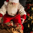 Santa Claus opening his sack and taking gifts — Stock Photo #36520405