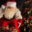 Santa Claus opening his sack and taking gifts — Stockfoto