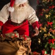 Santa Claus opening his sack and taking gifts — Stock Photo #36520413