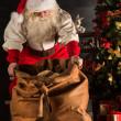 Santa Claus opening his sack and taking gifts — Stock Photo #36520425