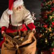 Santa Claus opening his sack and taking gifts — Stock Photo #36520435