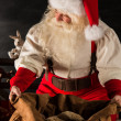 Santa Claus opening his sack and taking gifts — Stock Photo #36520437