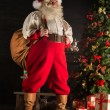 Real Santa Claus carrying big bag full of gifts — Stock Photo