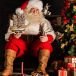 Santa Claus at home playing with new toys — Stockfoto