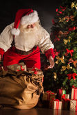 Santa Claus opening his sack and taking gifts — Stock Photo
