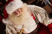 Santa Claus at home playing with new toys near Christmas Tree — Stock Photo
