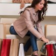 Image of lady trying on several pairs of new shoes in the store — Stock Photo