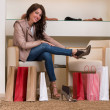 Image of lady trying on several pairs of new shoes in store — Stock Photo #36952051
