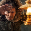Brutal man walking under snowstorm at night lighting his way with lantern — Stock Photo