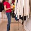 Woman shopping choosing dresses — Stock Photo