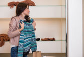 Woman shopping choosing sweater looking in mirror uncertain — Stock Photo