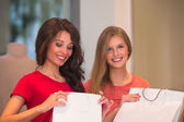 Young girls with shopping bags in store — Stock Photo