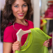 Woman shopping in an clothes store trying on new clothes — Stock Photo #37353691