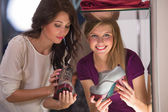 Two beautiful young girls choosing shoes at store — Stock Photo