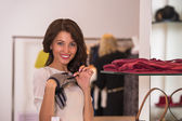 Young woman looking at the shop showcase and taking accessories — Stock Photo