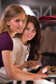 Two beautiful young girls choosing accessories at store — Stock Photo