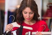 Mujer de compras en una tienda de ropa probándose ropa nueva — Foto de Stock
