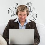 jonge zakenman luisteren naar muziek en werken in zijn kielzog — Stockfoto