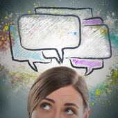 Portrait of pretty young girl looking at dialogue symbols overhead — Stock Photo